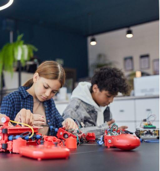 deux enfants qui apprennent a programmer un robot rouge