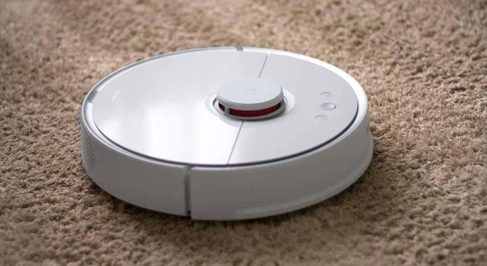laspirateur robot Roborock blanc de la marque Xiaomi qui aspire un tapis beige