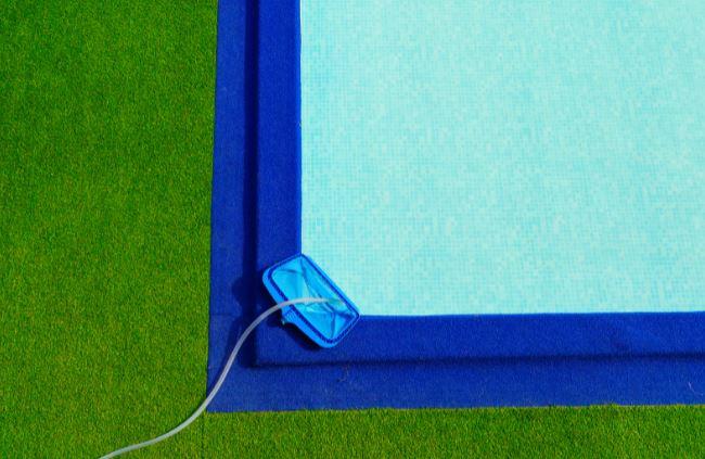 le filet de ramassage des impuretes dune piscine pose sur le bord du bassin bleu avec de lherbe synthetique tout autour