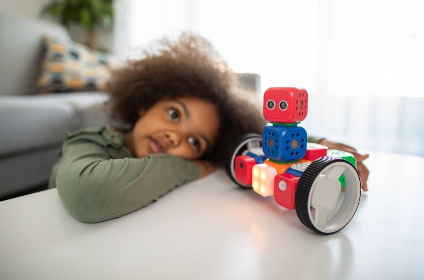 un enfant de 5 ans a cote dune table blanche qui tient un jouet robot avec des roues