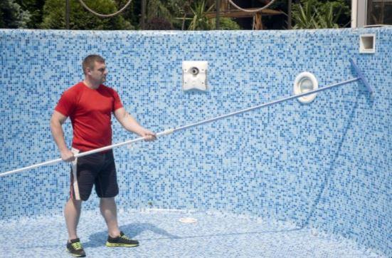 un homme dans une piscine carrelee vide en train de nettoyer les parois manuellement