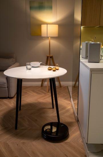 un robot aspirateur noir qui nettoie le salon dun petit appartement avec une petite table ronde aux pieds noir